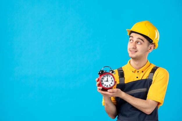 Vooraanzicht van mannelijke werknemer in uniform met klokken op blauw