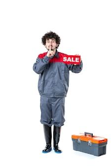 Vooraanzicht van mannelijke werknemer in uniform met verkoopnaambordje op lichte muur