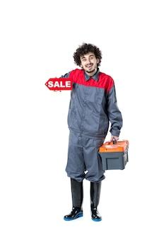 Vooraanzicht van mannelijke werknemer in uniforme gereedschapskoffer en verkoop op witte muur