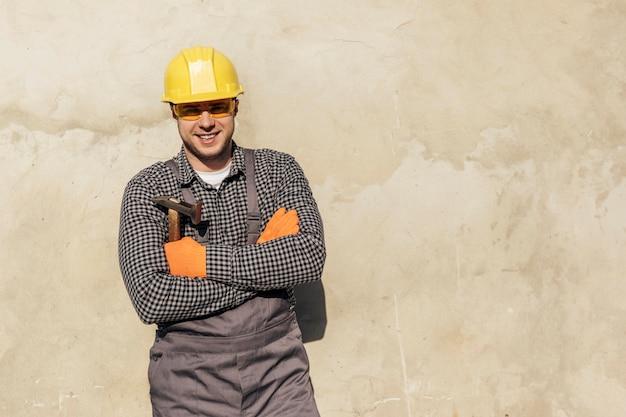 Vooraanzicht van mannelijke werknemer met bouwvakker en exemplaarruimte