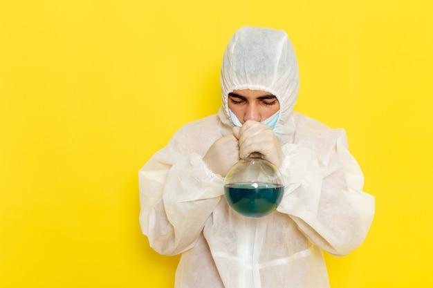Vooraanzicht van mannelijke wetenschappelijke werker in speciaal beschermend pak bedrijf kolf met oplossing ruiken het op gele muur