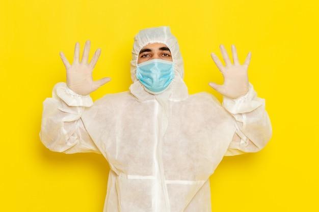 Vooraanzicht van mannelijke wetenschappelijke werker in speciaal beschermend pak en met masker dat zijn handen op lichtgele muur toont