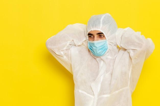 Vooraanzicht van mannelijke wetenschappelijke werker in speciaal beschermend pak en met masker moe op lichtgele muur