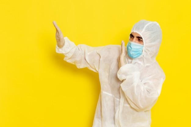 Vooraanzicht van mannelijke wetenschappelijke werker in speciaal beschermend pak en met masker op de lichtgele muur