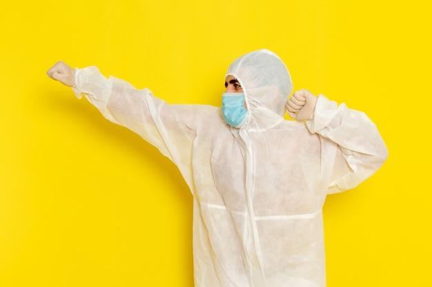 Vooraanzicht van mannelijke wetenschappelijke werker in speciaal beschermend pak en met masker poseren op lichtgele muur