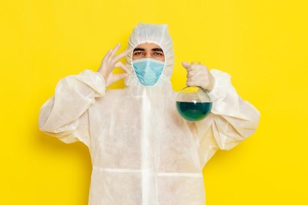 Vooraanzicht van mannelijke wetenschappelijke werker in speciaal beschermend pak met de kolf van de maskerholding op gele muur