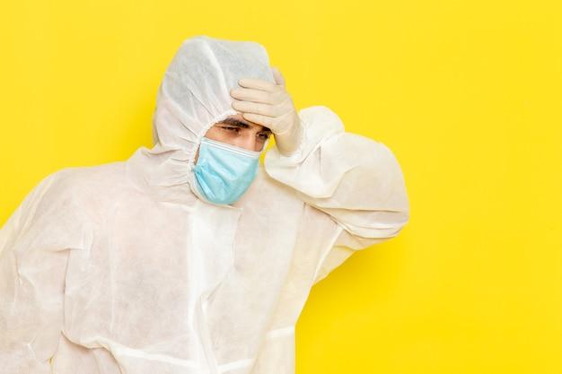Vooraanzicht van mannelijke wetenschappelijke werker in speciaal beschermend wit pak met steriel masker met hoofdpijn op gele muur