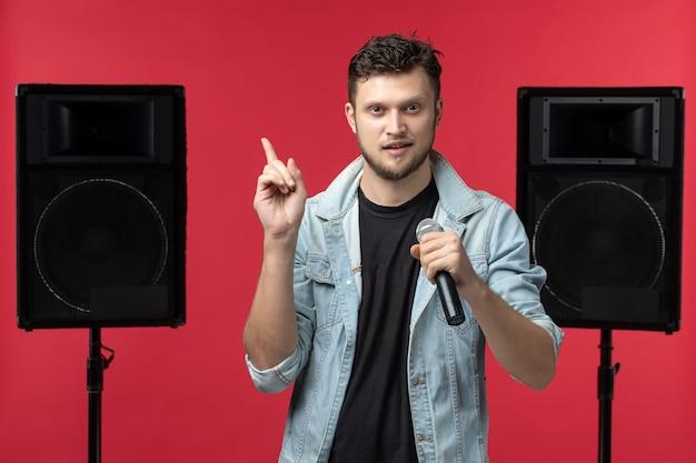 Vooraanzicht van mannelijke zanger die op het podium op de rode muur optreedt