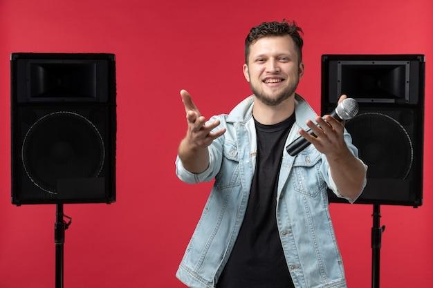 Vooraanzicht van mannelijke zanger die op het podium optreedt met microfoon op rode muur