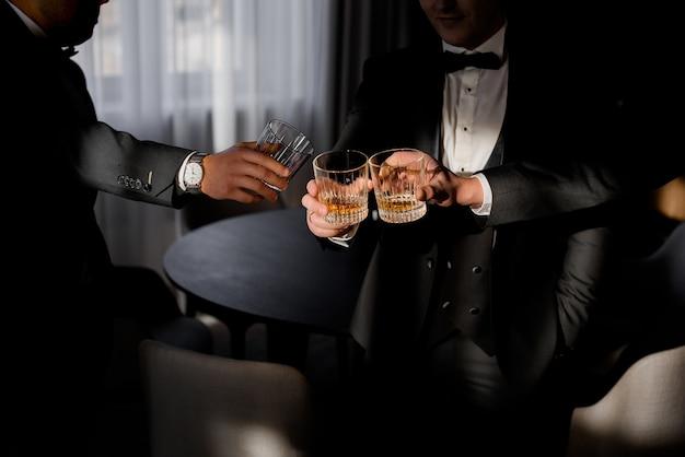 Vooraanzicht van mannen gekleed in zakelijke kostuums die whisky drinken