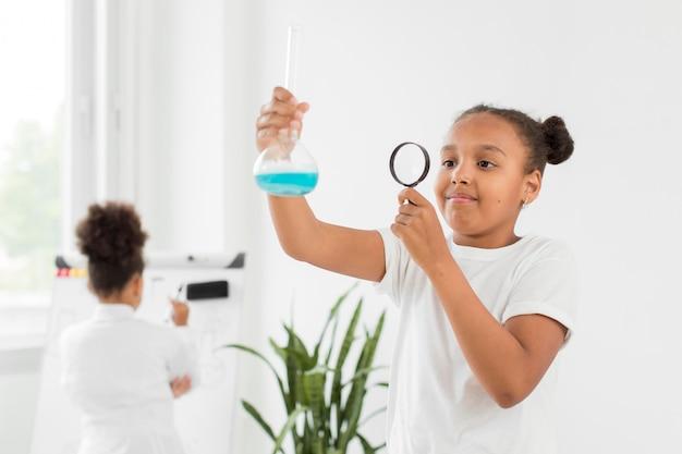 Vooraanzicht van meisje dat drankje in buis met vergrootglas bekijkt