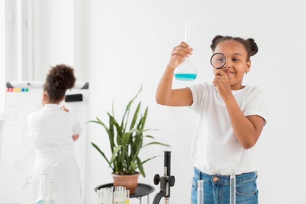 Vooraanzicht van meisje dat drankje met vergrootglas bekijkt