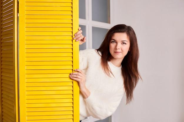 Vooraanzicht van meisje dat uit het gele scherm gluurt en naar de camera kijkt