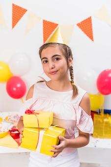 Vooraanzicht van meisje in de holdingsgiften van de partijhoed in verjaardagspartij