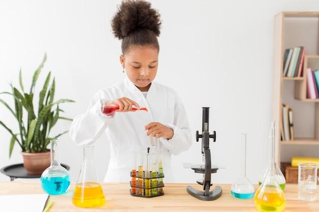 Vooraanzicht van meisje in laboratoriumjas die met drankjes experimenteren