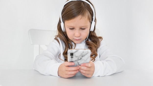 Vooraanzicht van meisje met behulp van smartphone en koptelefoon thuis