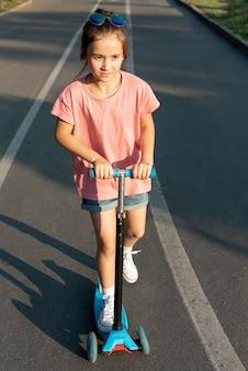 Vooraanzicht van meisje op blauwe scooter