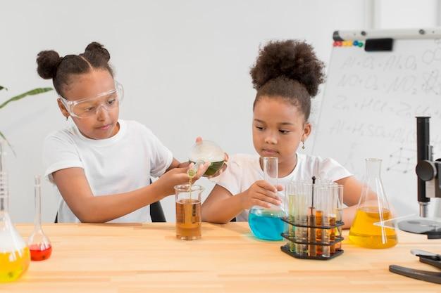 Vooraanzicht van meisjes die chemie met buizen en drankjes experimenteren