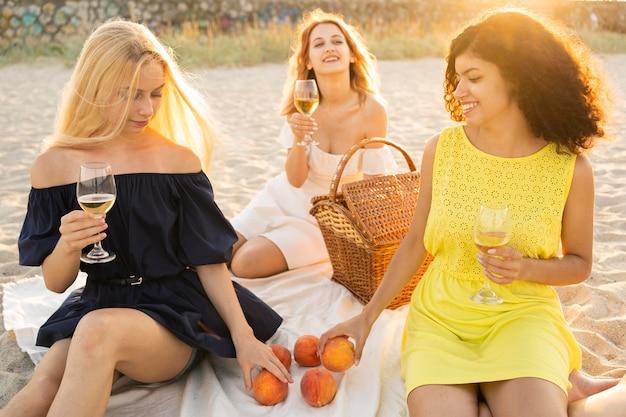 Vooraanzicht van meisjes die een picknick hebben bij strand