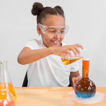 Vooraanzicht van meisjeswetenschapper die met drankjes experimenteren