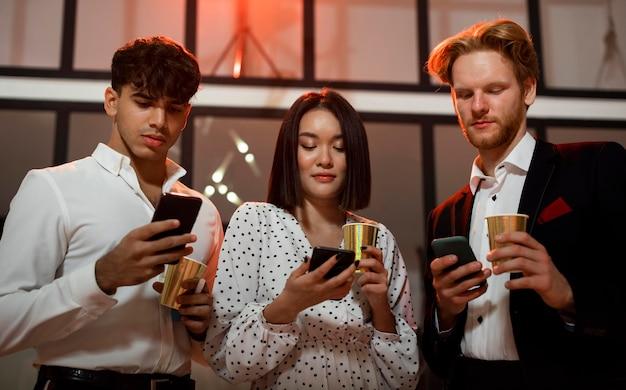 Vooraanzicht van mensen die hun familieleden berichten sturen op oudejaarsavondfeest