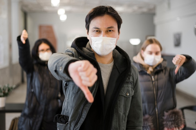 Vooraanzicht van mensen die medische maskers dragen en duimen neergeven