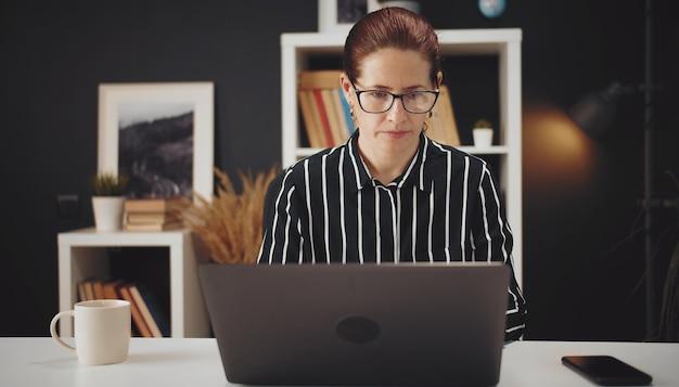 Vooraanzicht van middelbare leeftijd ernstige vrouw die op laptop werkt vanuit huis aan tafel zitten, e-werk