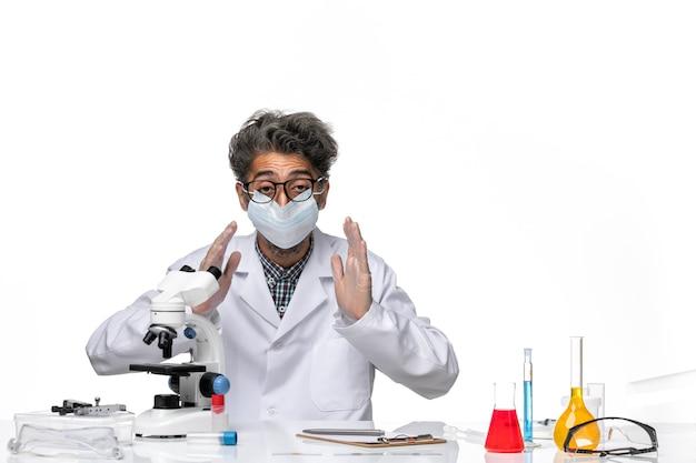 Vooraanzicht van middelbare leeftijd wetenschapper in speciaal pak aan tafel zitten met oplossingen