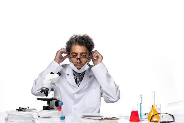 Vooraanzicht van middelbare leeftijd wetenschapper in speciaal pak rond de tafel zitten met microscoop en oplossingen