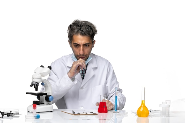 Vooraanzicht van middelbare leeftijd wetenschapper in wit medisch pak rond de tafel zitten met oplossingen
