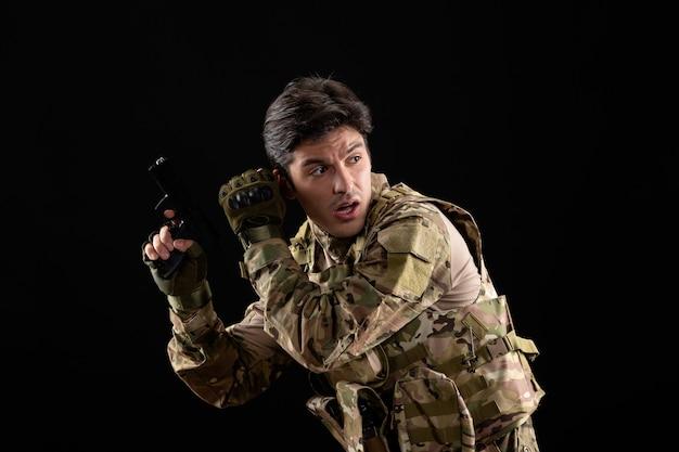 Vooraanzicht van militaire militair in uniform met pistool op zwarte muur