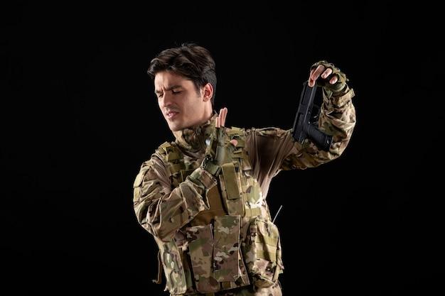 Vooraanzicht van militaire militair in uniform met zwarte pistool zwarte muur