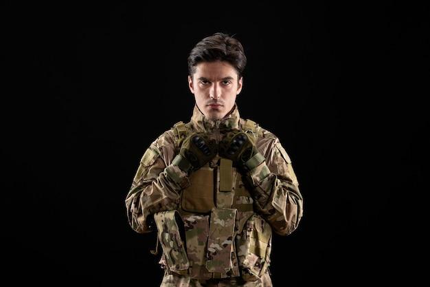 Vooraanzicht van militaire militair in uniform op zwarte muur