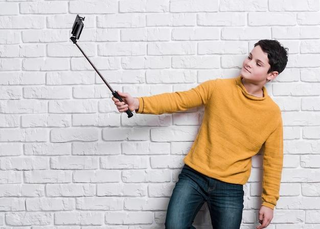 Vooraanzicht van moderne jongen die een selfie neemt