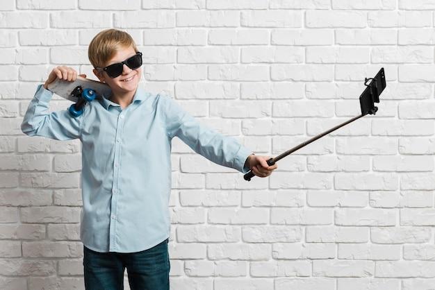 Vooraanzicht van moderne jongen met skateboard dat selfie neemt