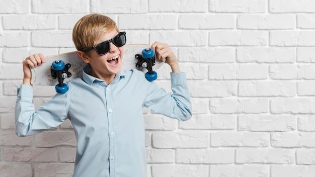 Vooraanzicht van moderne jongen met skateboard en exemplaarruimte