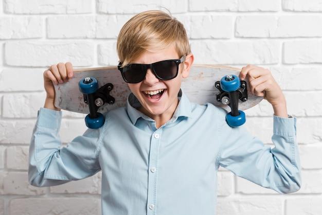 Vooraanzicht van moderne jongen met skateboard en zonnebril