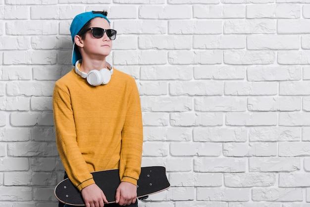 Vooraanzicht van moderne jongen met skateboard met exemplaarruimte