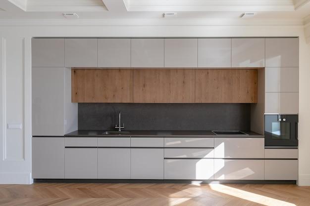Vooraanzicht van moderne premium keuken in klassiek interieur met houten meubilair en frans visgraatparket