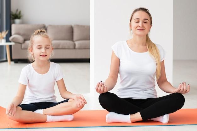 Vooraanzicht van moeder die yoga met dochter thuis doet