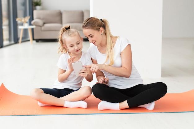Vooraanzicht van moeder en dochter thuis bij yogamat het spelen op smartphone