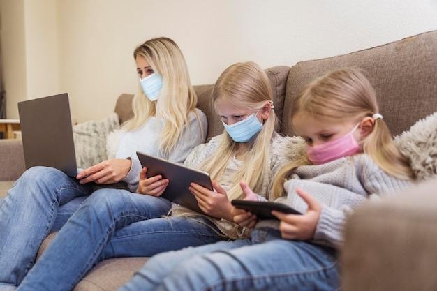 Vooraanzicht van moeder en dochters met technologie