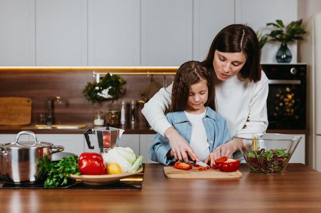 Vooraanzicht van moeder en meisje die voedsel in de keuken bereiden