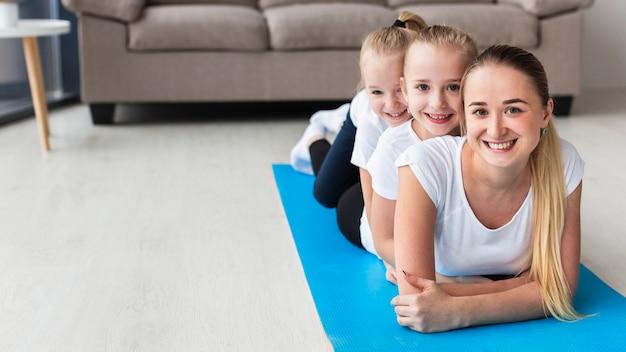 Vooraanzicht van moeder het stellen met dochters thuis op yogamat