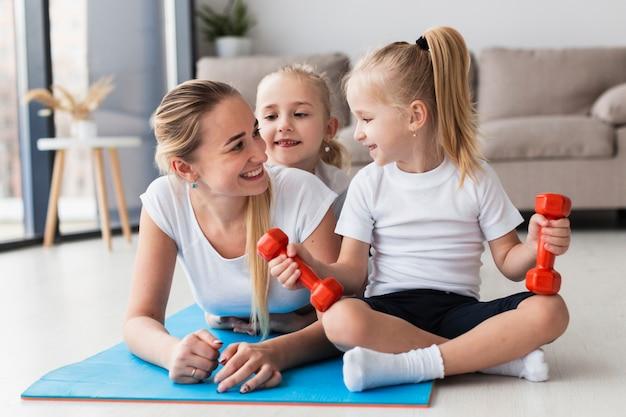 Vooraanzicht van moeder het stellen met dochters thuis