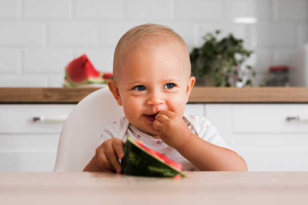 Vooraanzicht van mooie baby die watermeloen eet