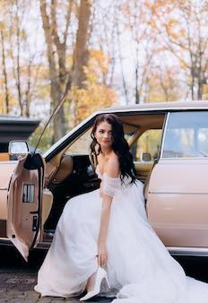 Vooraanzicht van mooie brunette bruid zit op de voorbank van de roze auto en past haar schoen aan