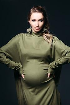 Vooraanzicht van mooie en modieuze zwangere donkerbruine vrouw bij donkere studio. mooie en stijlvolle vrouw die in kaki kleding draagt, die zwangere buik houdt, die camera bekijkt. concept van de zwangerschap