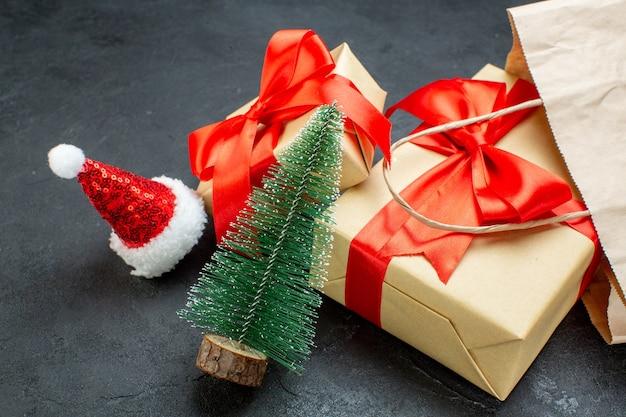 Vooraanzicht van mooie geschenken met rood lint en kerstboom kerstman hoed op een donkere tafel
