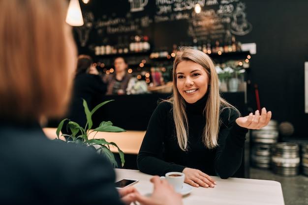 Vooraanzicht van mooie jonge vrouw die aan een vriend bij de koffie spreekt.